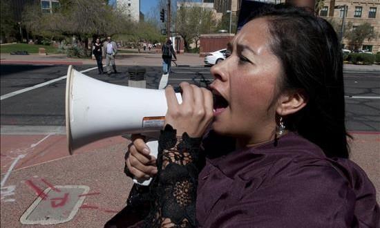 La activista Dulce Matuz, cofundadora de la Coalición del Acta Sueño habla por un megáfono.