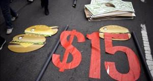 Nuevos grupos se suman al reclamo de 15 dólares por hora en Chicago Fotografías de señales usadas por trabajadores miembros de sindicatos durante una manifestación exigiendo practicas laborales justas y el aumento de salario mínimo a 15 dólares la hora.