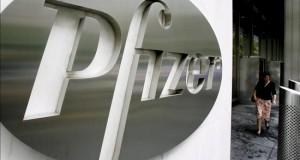 Pfizer anuncia fusión con Allergan, en operación por 160.000 millones dólares Una mujer pasa al lado del logotipo de Pfizer, en su sede general de Nueva York, EE.UU.
