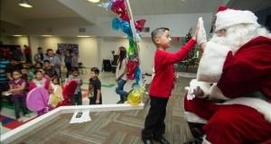 """Cientos de niños inmigrantes pasarán la navidad en centros de detención Un niño saluda un Papa Noél o Santa Claus durante el evento denominado """"La Mejor Navidad de Todas""""."""