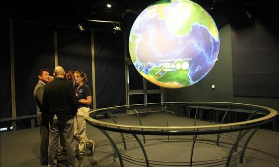 La Tierra ha entrado en una nueva época geológica, según los científicos Investigadores conversan junto a un globo terráqueo de alta tecnología.
