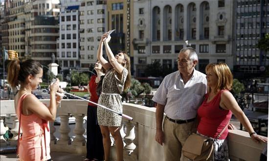 El turismo mundial creció un 4,4 % en 2015 y roza 1.200 millones de viajeros Un grupo de personas visita el balcón del Ayuntamiento de Valencia.