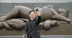"""Botero abre en Shanghái su primera muestra con escultura monumental en China Un visitante se fotografía junto a una de las nueve esculturas monumentales del pintor y escultor colombiano Fernando Botero que se exponen desde hoy en el Museo de Arte de China en Shanghái, como parte de la muestra """"Botero en China"""", que podrá verse hasta el 8 de mayo."""