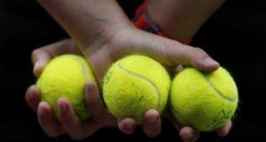 Una recogepelotas sujeta tres bolas durante un partido. EFE/Archivo