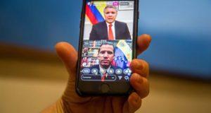 Una mujer sostiene un teléfono inteligente donde se ve una transmisión en vivo de una conversación a través de la red social Instagram entre el presidente de Colombia Iván Duque (arriba) y el jefe del Parlamento venezolano Juan Guaidó este viernes en Caracas (Venezuela). EFE