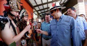 Fotografía distribuida por Casa Presidencial de una mujer que muestra al presidente Juan Orlando Hernández (d), este sábado durante la inauguración del II Festival Internacional de Chocolate Artesanal, en el municipio Santa Cruz de Yojoa en el norte de Honduras. EFE/ Presidencia