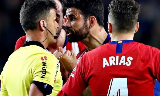 El delantero hispano-brasileño del Atlético de Madrid, Diego Costa (2d), protesta una jugada al colegiado Gil Manzano, acción que le costó la expulsión al delantero rojiblanco durante el encuentro correspondiente a la jornada 31 de primera división que disputaron frente al FC Barcelona en el estadio del Camp Nou, en Barcelona. EFE
