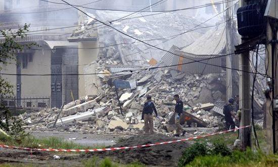 Miembros de las fuerzas de seguridad paquistaníes inspeccionan un edificio (d) antes de derrumbarse por una explosión este jueves, en el ámbito de una operación antiterrorista en Peshawar (Pakistán). Hoy, 14 pasajeros de varios autobuses han sido asesinados. EFE