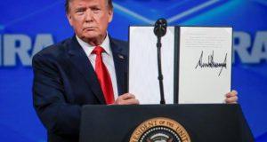 El presidente estadounidense, Donald Trump, muestra una resolución firmada tras su discurso ante el encuentro anual de la Asociación Nacional del Rifle (NRA) en Indianapolis (Estados Unidos), este viernes. EFE